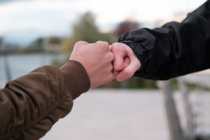 fist bump close-up. young people say hello fist outdoors fist. respect